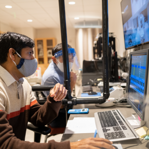 UMass researchers who are wearing facemasks working on computers