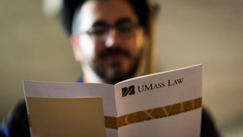 UMass Law graduate reading a commencement pamphlet