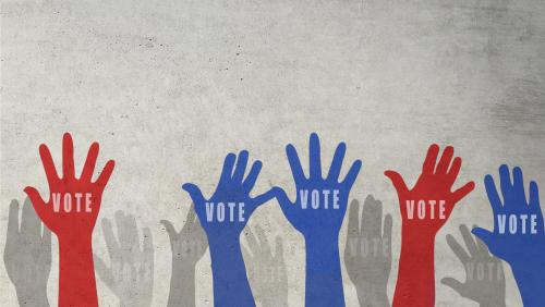 """Red and blue hands raised that say """"Vote"""" on the palms"""