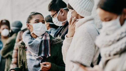 Students wearing masks wait in line outside
