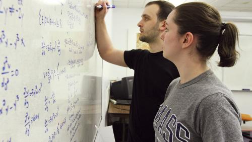 Two students write on white board in classroom