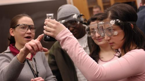 Group of students work in lab together and examine beaker