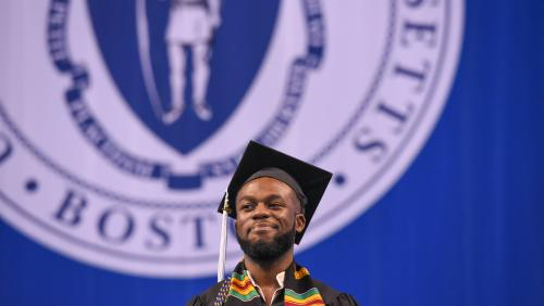 Student smiling on stage of UMass Boston commencement
