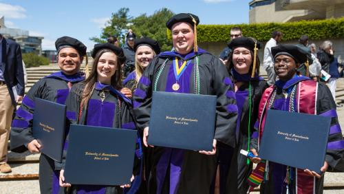 A group of UMass Law students smiling with their degrees after commencement ceremony