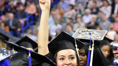 UMass Lowell graduate holds up peace sign at commencement