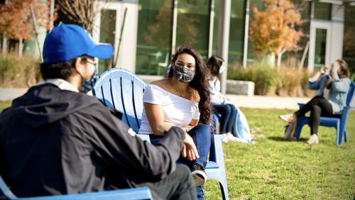 Two students sit outside on campus wearing masks