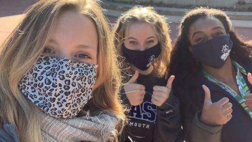 Three students smile at camera while wearing masks