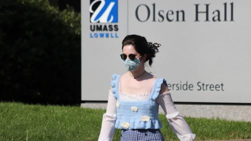 Student walks on campus while wearing a mask