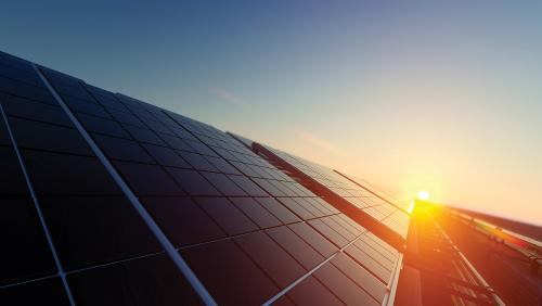 Stock image of a sunset behind a solar panel
